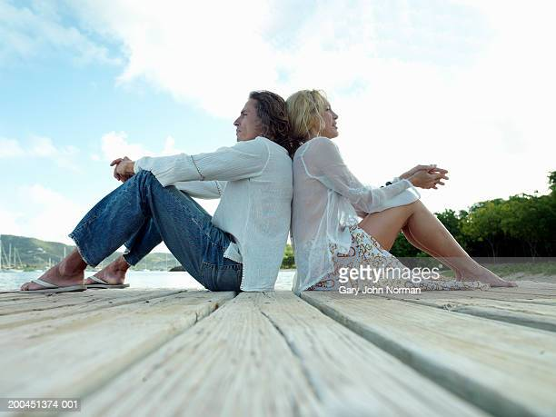 Couple sitting on dock, side view