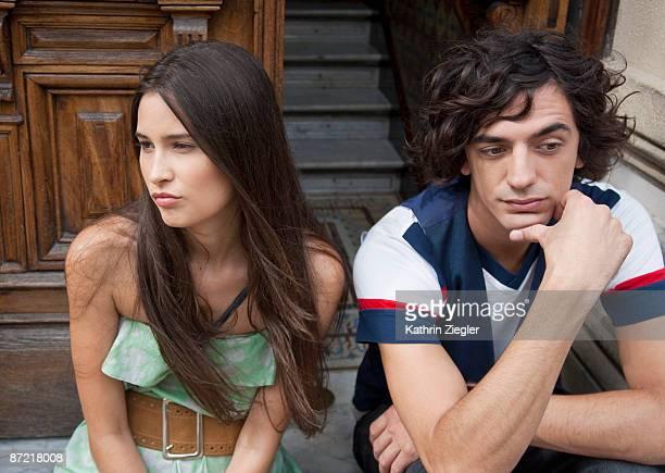 couple sitting on doorstep, having a dispute