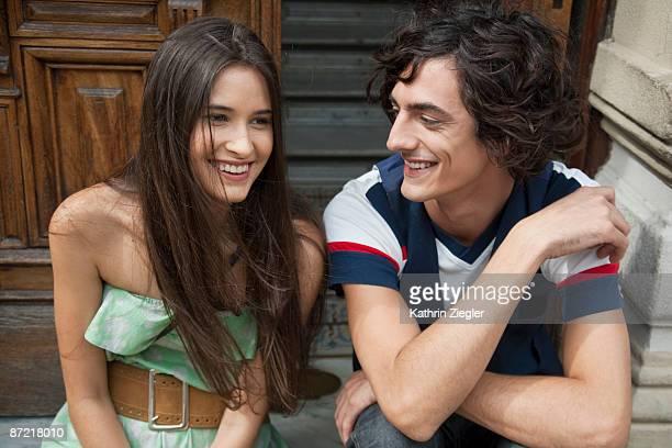 couple sitting on doorstep, laughing