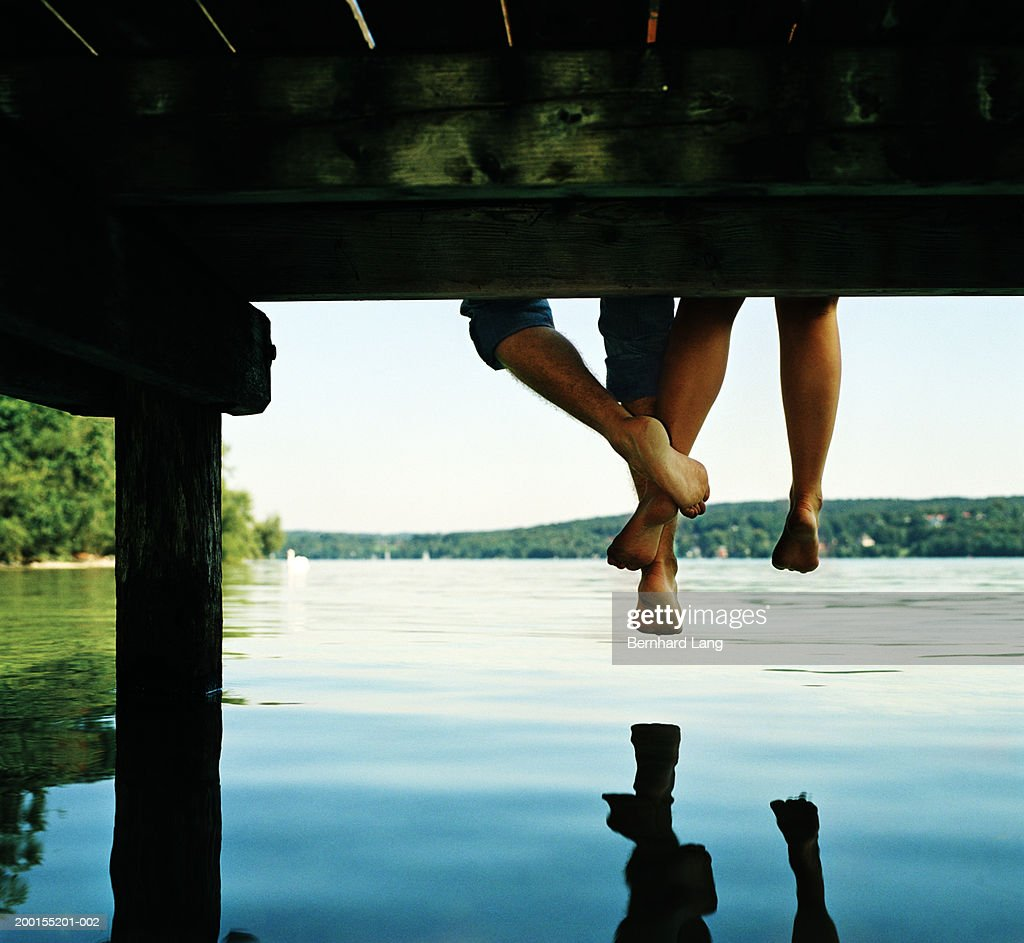Couple sitting on edge of jetty, legs touching, low section : Stock Photo