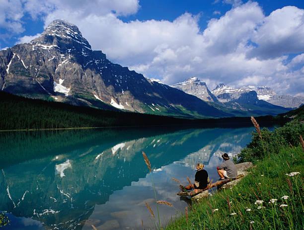 Couple sitting on edge of Waterfowl Lake, Banff National Park, Canada
