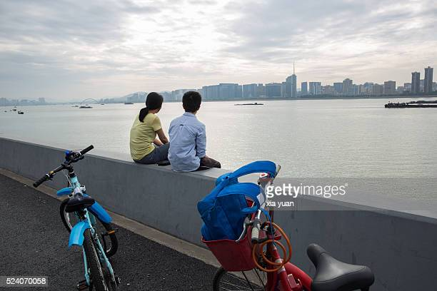 A couple sitting on embankments of Qianjiang river with bikes,Hangzhou,China