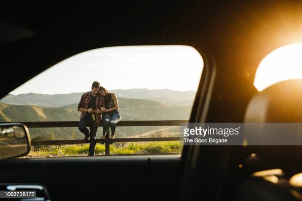 couple sitting on fence taking selfie on road trip - love emotion stock pictures, royalty-free photos & images