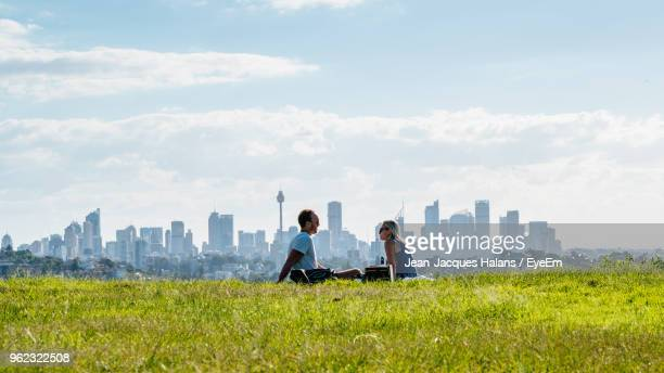couple sitting on field - sydney stock pictures, royalty-free photos & images