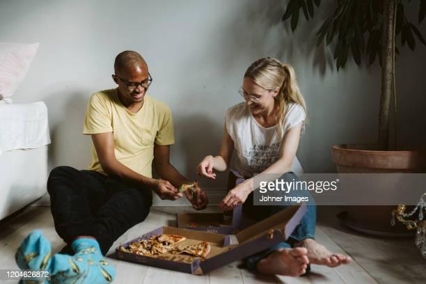 couple sitting on floor and having pizza - relationship stockfoto's en -beelden