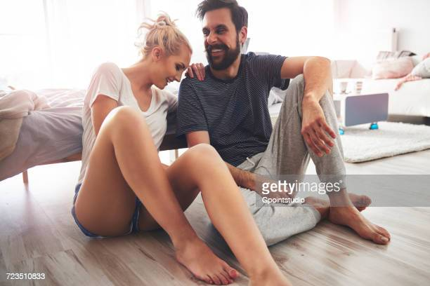 Couple sitting on floor beside bed, laughing