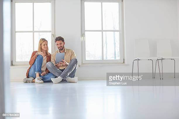 Couple sitting on floor browsing digital tablet in empty new home