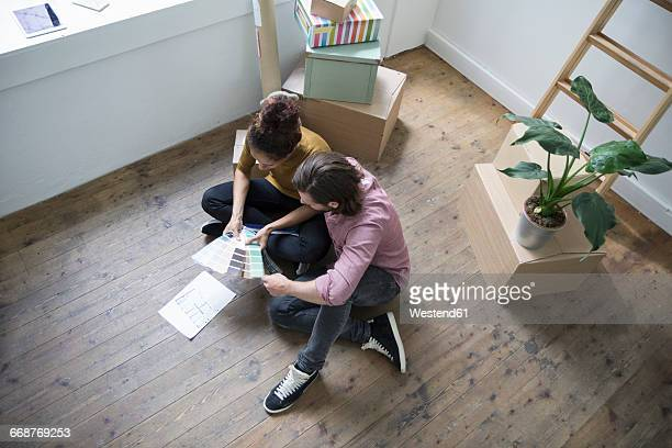 Couple sitting on floor of new flat choosing from color samples