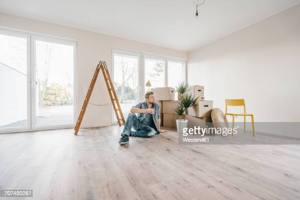 Couple sitting on floor of their new home among moving boxes