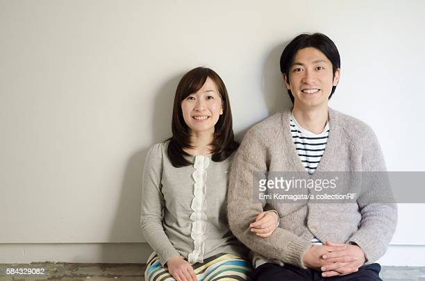 Couple sitting on floor, smiling