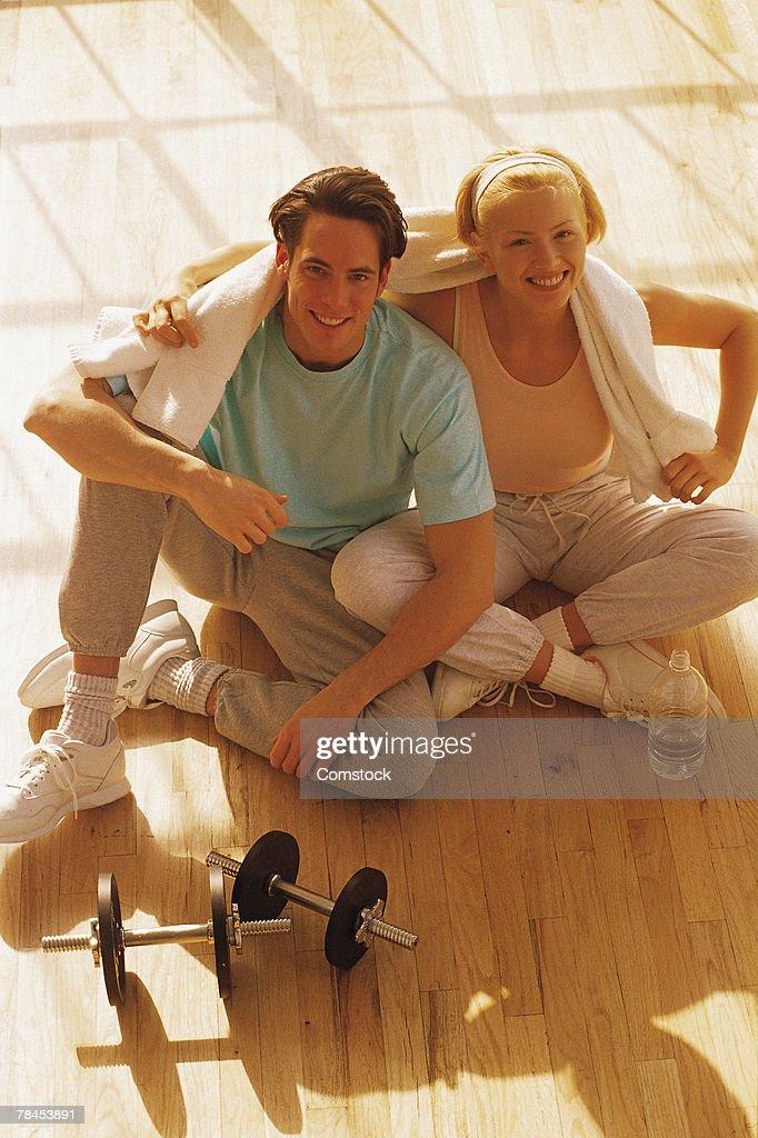 Couple sitting on floor with dumbbells : Stockfoto