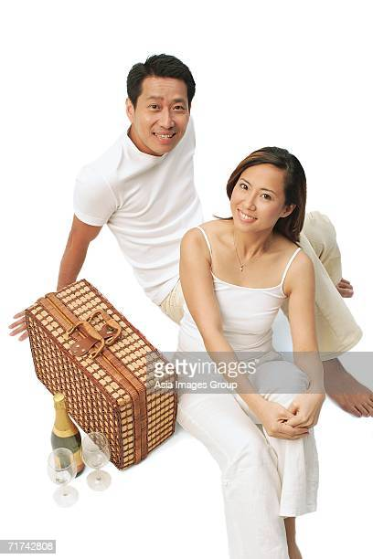 Couple sitting on floor with picnic basket, wine bottle and glasses