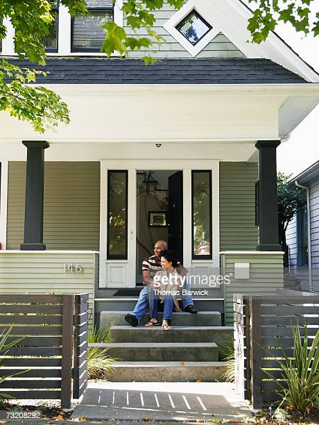 Couple sitting on front doorstep of home