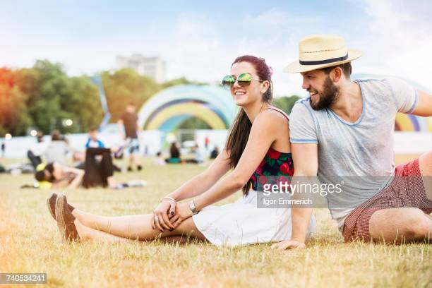 Couple sitting on grass together at festival