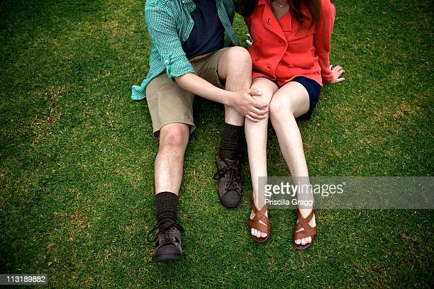 couple sitting on grass together - knees together stock photos and pictures