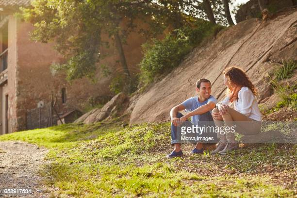 Couple sitting on grassy field against rock