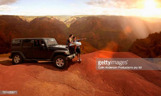 Couple sitting on hood of car reading map