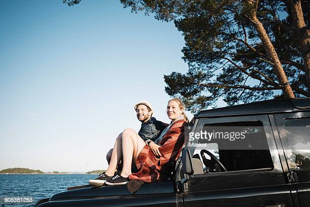 couple sitting on jeep at lakeshore against clear blue sky - wonderlust stock photos and pictures