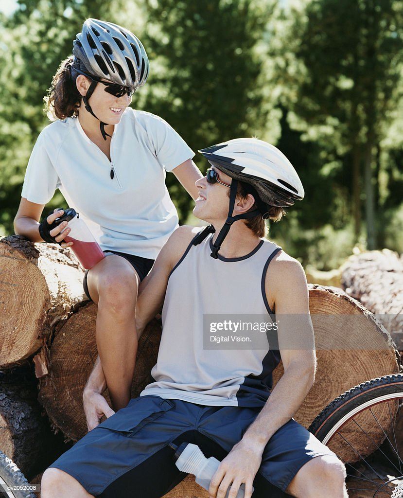 Couple Sitting on Logs in a Forest With Their Mountain Bikes : Stock Photo