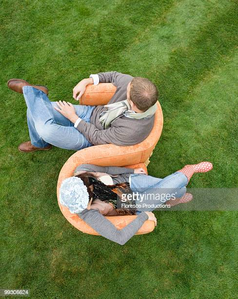 Couple sitting on love-seat outdoors