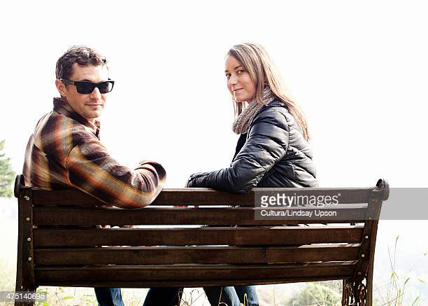Couple sitting on park bench and looking over their shoulder