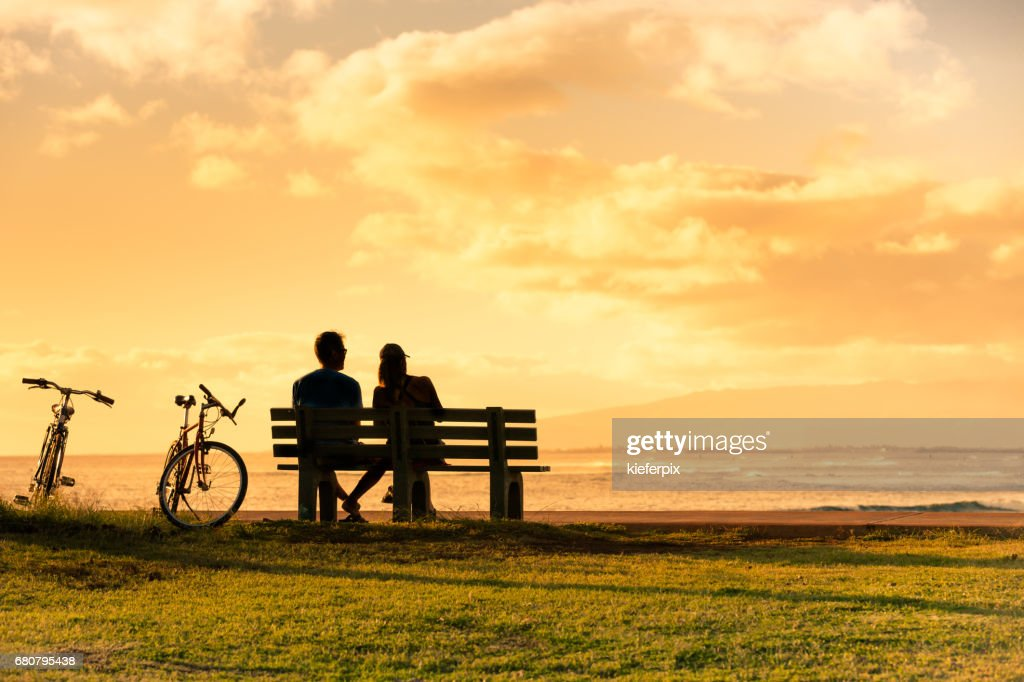 Couple sitting on park bench watching the sunset. : Stock Photo