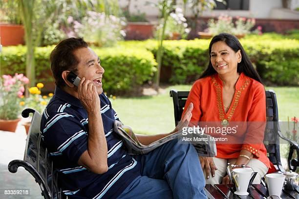 couple sitting on patio, man on phone - indian couples stock pictures, royalty-free photos & images