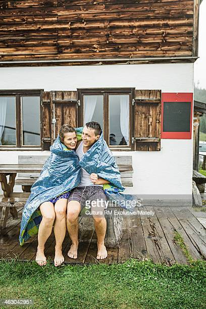 Couple sitting on picnic bench in rain, Tyrol, Austria