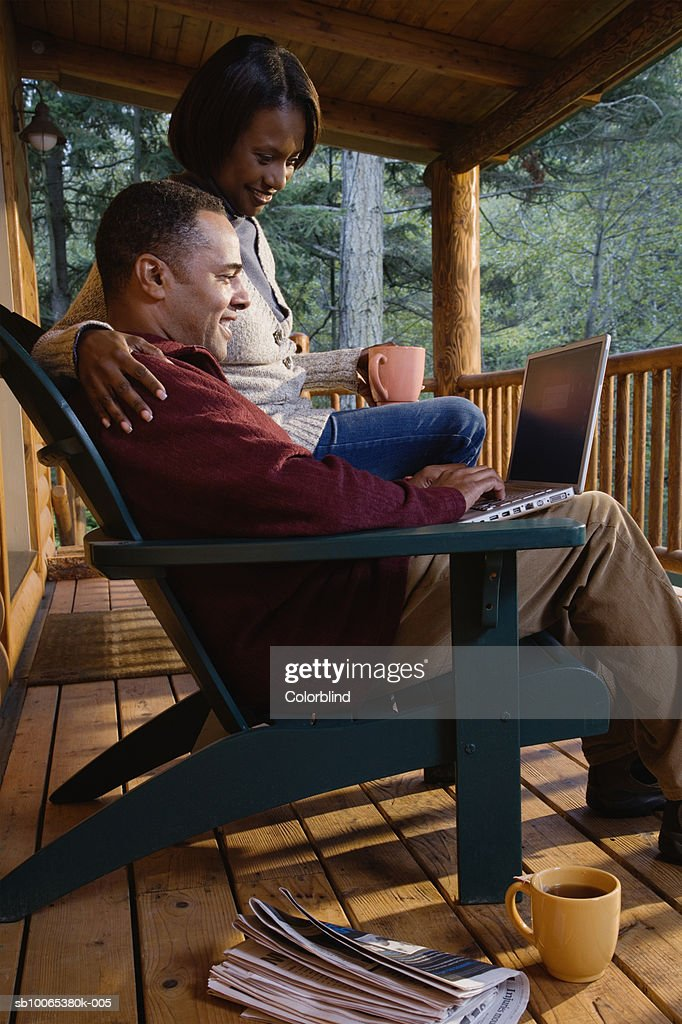 Couple sitting on porch, man working on laptop : Foto stock