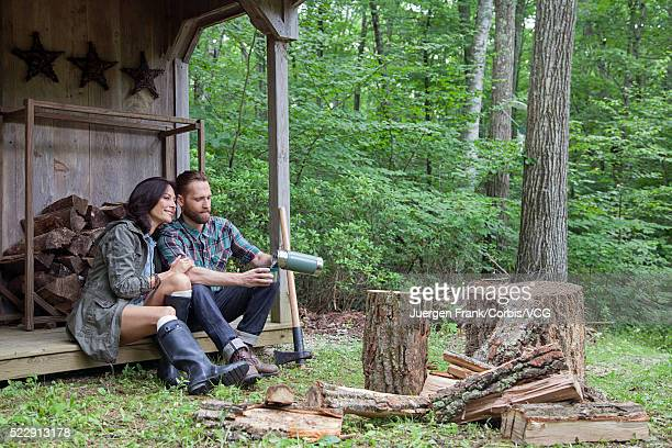 Couple sitting on porch of log cabin