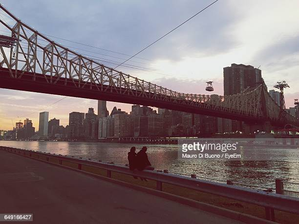 Couple Sitting On Retaining Wall At Roosevelt Island With Queensboro Bridge Over East River