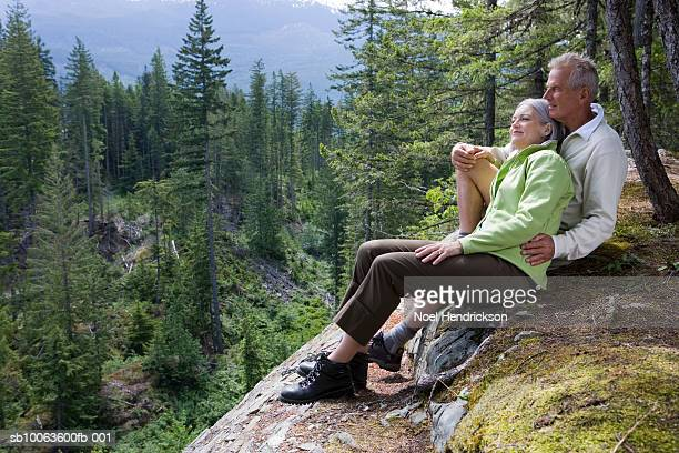 Couple sitting on rock, embracing, looking at view