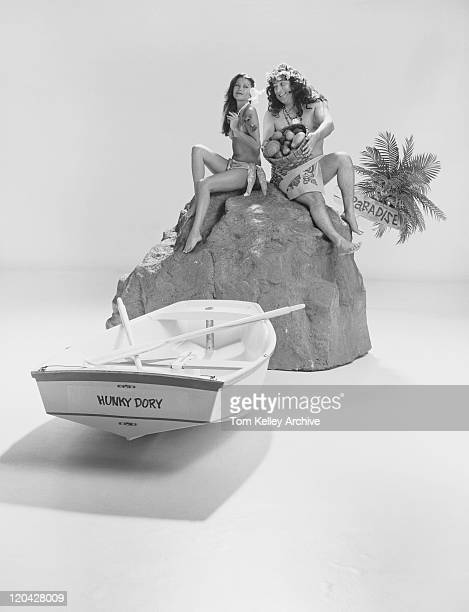 Couple sitting on rock with fruits basket