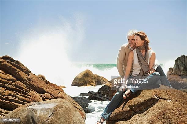 Couple sitting on rocks at beach
