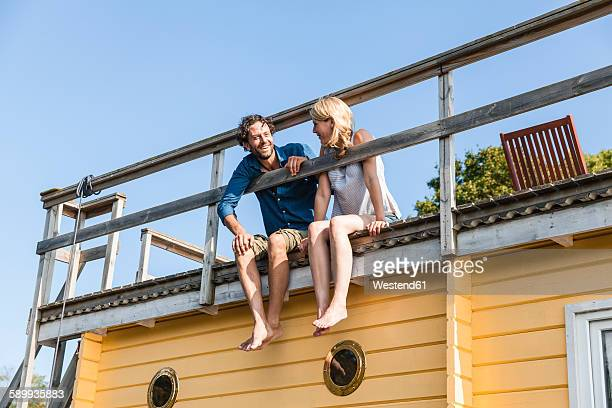 couple sitting on roof deck of a house boat - houseboat stock pictures, royalty-free photos & images