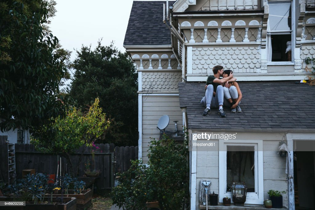 Couple sitting on roof kissing : Stock Photo