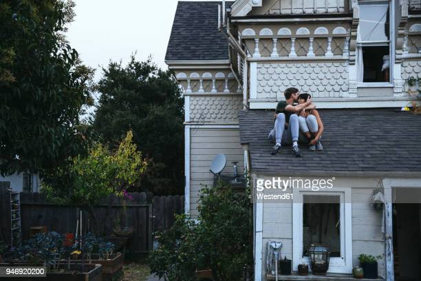 couple sitting on roof kissing - freaky couples stockfoto's en -beelden