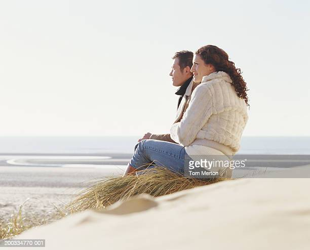 Couple sitting on sand dune, side view (focus on couple)