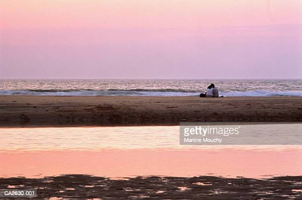 couple sitting on sandy beach at sunset, rear view - romantic sky stock pictures, royalty-free photos & images