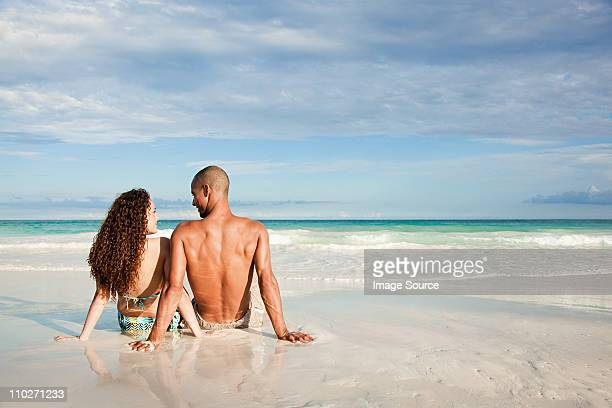 Couple sitting on sandy beach at water's edge