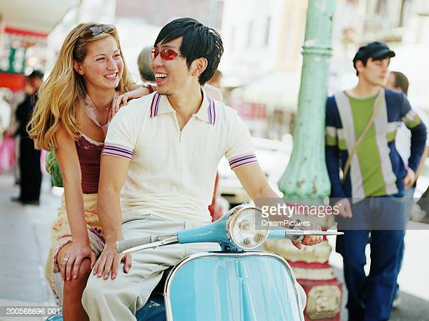 Couple sitting on  scooter on street, smiling