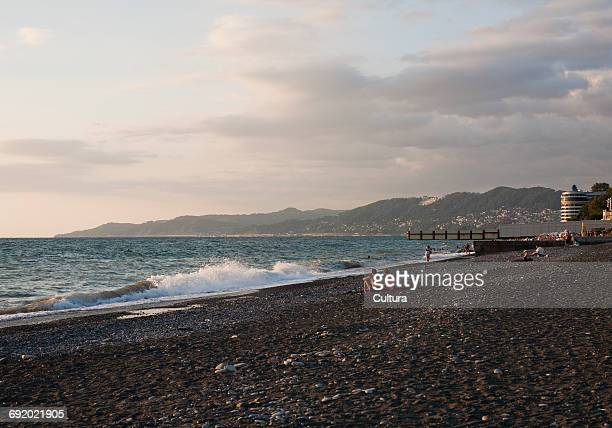 Couple sitting on shingle beach looking at view of black sea, Sochi, Russia