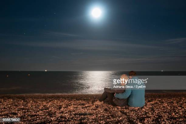 couple sitting on shore against sky at night - moonlight stock pictures, royalty-free photos & images