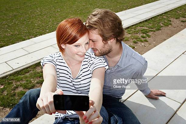 Couple sitting on sidewalk photographing themselves