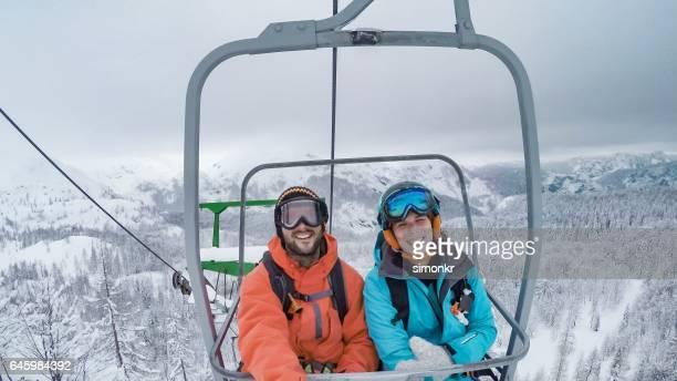 Couple assis sur les remontées mécaniques