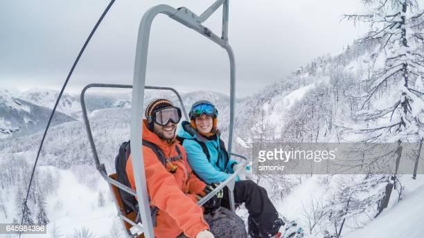 Couple sitting on ski lift