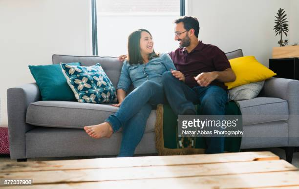 Couple sitting on sofa and enjoying the time together.