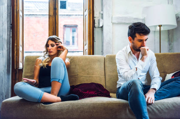 Couple sitting on sofa apart and being angry after quarrel
