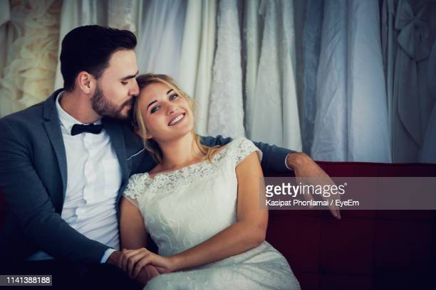 couple sitting on sofa at home - groom stock pictures, royalty-free photos & images