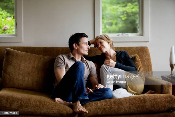 couple sitting on sofa at home - esposa imagens e fotografias de stock